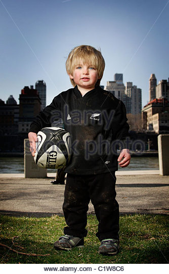 A two year old rugby player in a New Zealand All Blacks kit - Stock Image