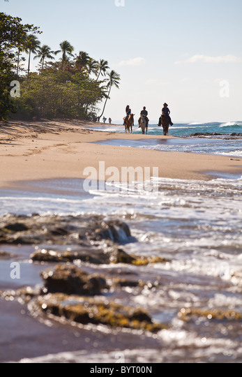 Horseback riders at Las Marias beach in Rincon Puerto Rico - Stock Image