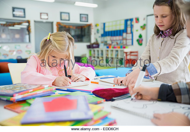 Elementary students drawing in classroom - Stock-Bilder