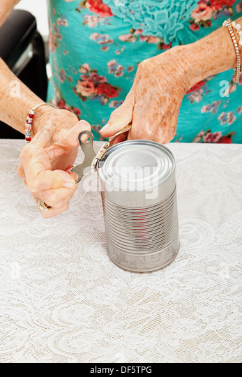 Closeup of senior woman's hands as she struggles to open a can with her painful arthritis.  - Stock Image