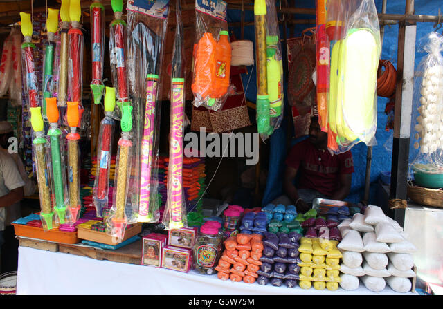 A small streetside shop selling traditional colors and toys for the celebration of HOLI festival in India. - Stock-Bilder