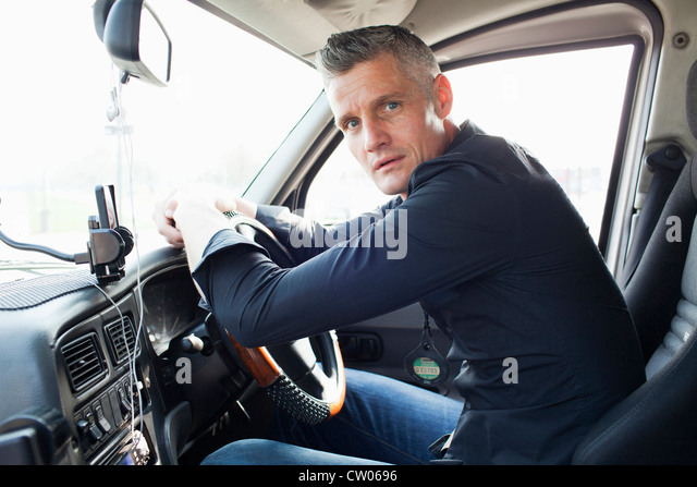 Taxi driver sitting at steering wheel - Stock Image