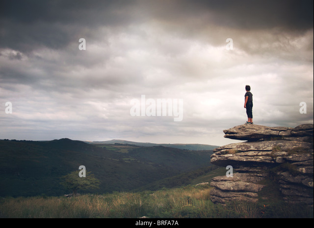 boy stood on the rocks looking over moors - Stock-Bilder