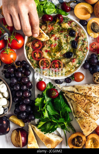 Eggplant babaganoush with red bell pepper and herbs on a snack board full of summer fruit photographed from top - Stock Image