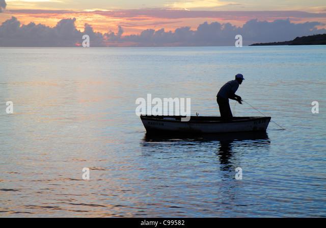 Curaçao Netherlands Antilles Dutch Piscadera Bay Caribbean Sea rowboat man fisherman sunset twilight calm ocean - Stock Image