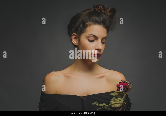 Beautiful Young Fashion Model Looking At Red Rose Against Gray Background - Stock Image