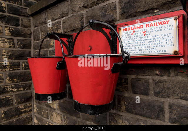 View of 2 old red & black fire buckets hanging on platform wall at quaint, historic Oakworth Station - Keighley - Stock Image