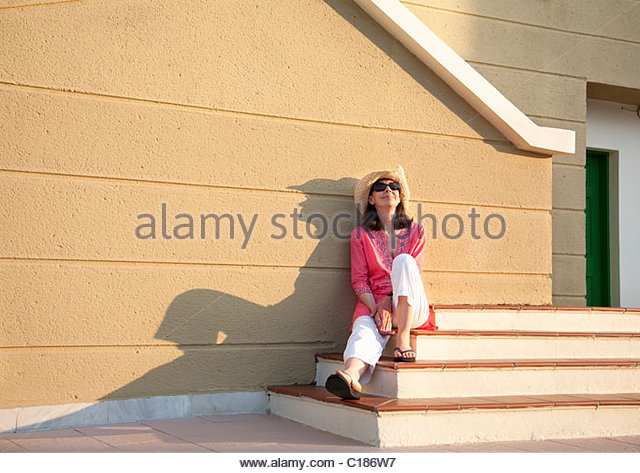 Woman relaxing in late afternoon sun - Stock Image