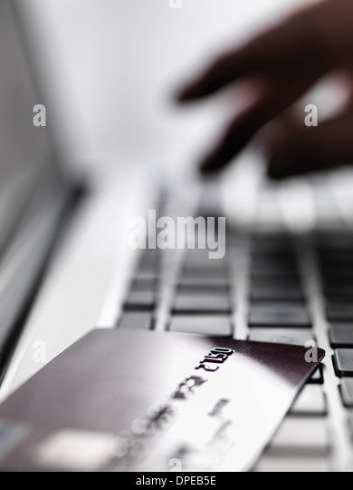 Hand tapping account details on laptop to illustrate internet shopping and internet fraud - Stock-Bilder
