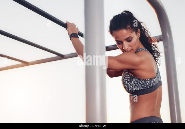 Portrait of strong young woman standing by monkey bar exercise equipment outdoors. Fitness woman in sportswear looking - Stock Image