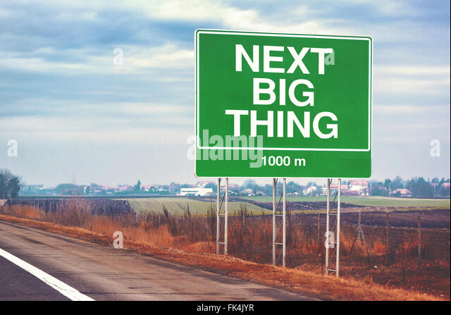 Next big thing ahead conceptual motivational image with road sign by the highway, retro toned image with selective - Stock Image