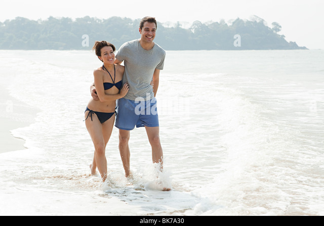 Couple walking in the sea - Stock Image