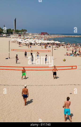 People playing volleyball on Platja Nova Icaria beach, Port Olimpic, Barcelona, Spain Europe - Stock Image