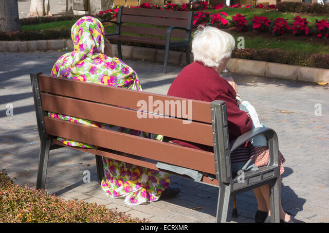 Elderly Spanish woman and woman from Western Sahara sitting on seat in Las Palmas, Gran Canaria, Canary Islands, - Stock-Bilder