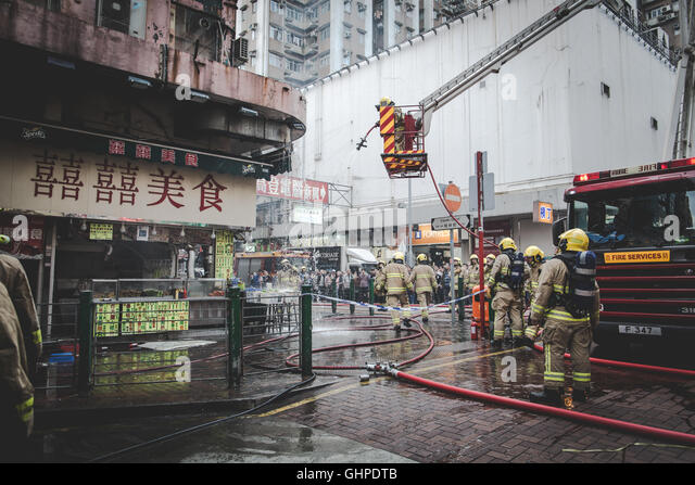 Fire fighters extinguish fire from a shop in Sham Shui Po, Hong Kong - Stock Image