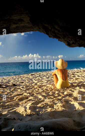 St Maarten cupecoy beach woman in straw hat sits outside rocky cave formation - Stock Image
