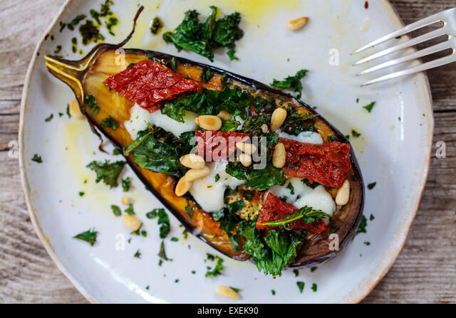Roast aubergine with goat cheese, crispy kale, sun dried tomatoes and pine nuts - Stock-Bilder