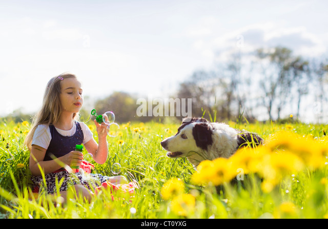 Girl blowing bubbles with dog in field - Stock Image