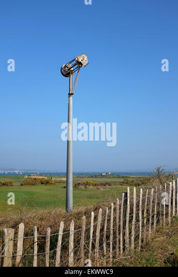 remains of a wind turbine damaged by coastal winds and weather against a blue sky - Stock Image