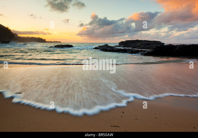 Kauai, HI Evening light on Lumaha'i Beach with sky colors reflecting on waves - Stock Image