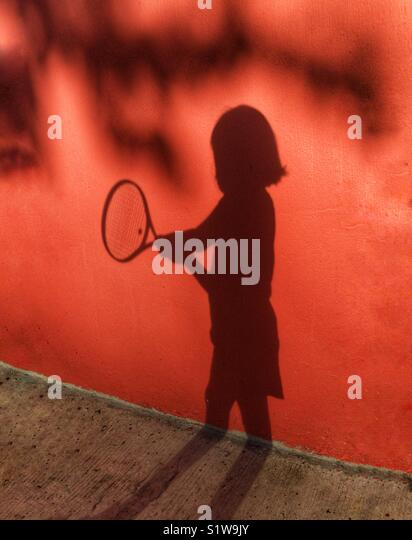 Shadow play of child holding tennis racket - Stock Image