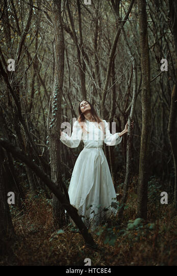 Romantic woman looking for nature wisdom. Ethereal forest - Stock-Bilder