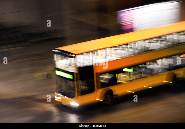 Panning shot of a bus by night, Berlin, Germany - Stock Image