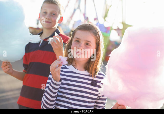Brother and sister eating pink candyfloss at fairground - Stock Image