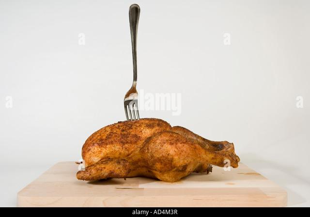 A fork stuck in a roast chicken - Stock-Bilder