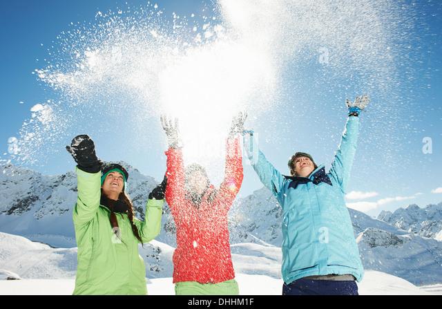 Female friends throwing snow mid air, Kuhtai, Austria - Stock Image