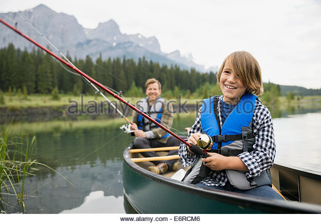 Father and son fishing in canoe in lake - Stock Image
