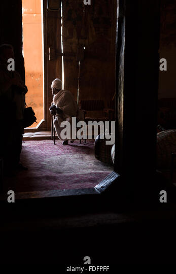 A priest sits in the dim light near an open door inside a rock-cut church near Wukro, Ethiopia. - Stock Image