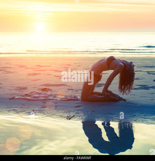 Young girl performs yoga exercises on the beach during sunset. Yoga, fitness and a Healthy lifestyle. - Stock Image