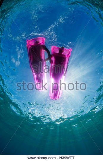 underwater perspective of two people relaxing on the ocean on pink inflatable mattresses - Stock Image