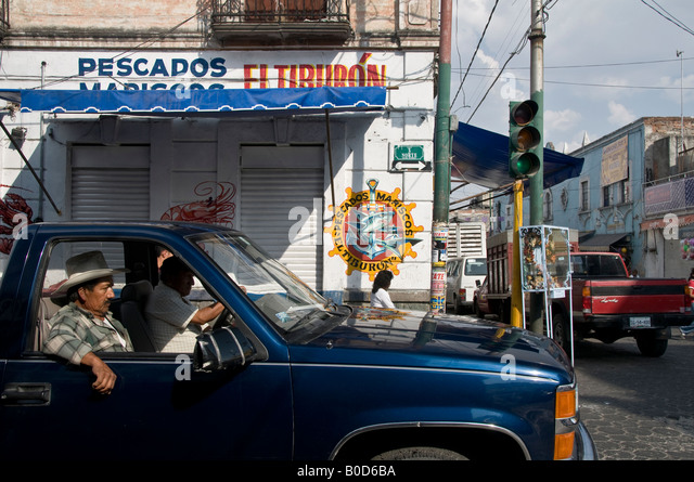 Two Mexican men sat in old pick-up truck waiting at the traffic lights. One wearing a cowboy Stetson hat. - Stock Image