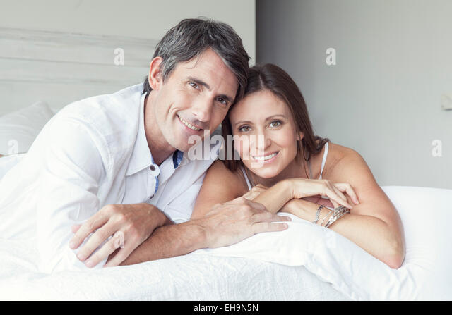 Couple lying on bed, portrait - Stock-Bilder