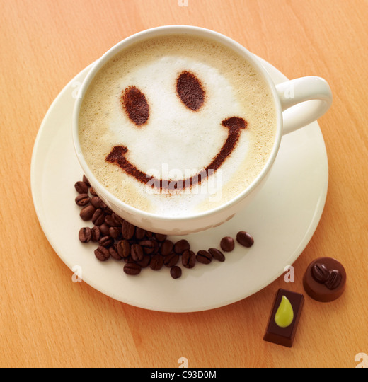 Cappuccino coffee with a chocolate powder smiley face on top with coffee beans and chocolates. - Stock Image
