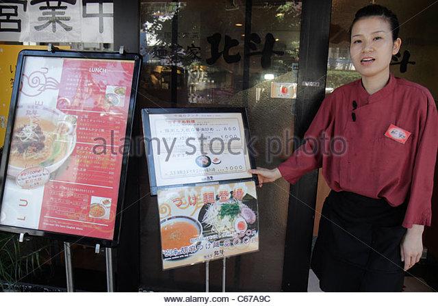 Tokyo Japan Harajuku Takeshita Dori Street restaurant entrance front Asian woman hostess waitress employee sign - Stock Image