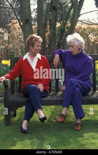 elderly women sitting on bench talking - Stock Image