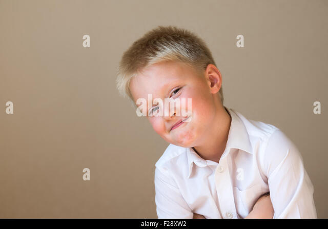 cunning sly smiling happy smart child boy on gray background - Stock Image