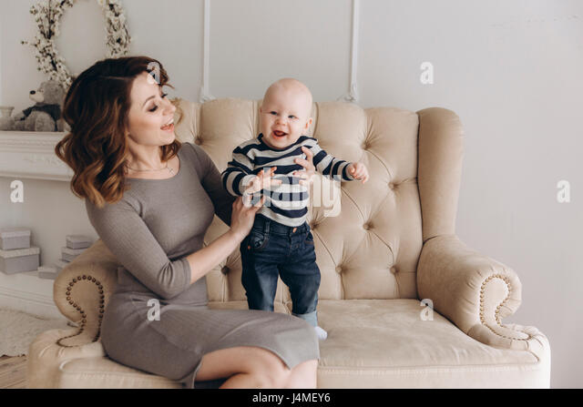 Caucasian mother sitting on love seat playing with baby son - Stock-Bilder