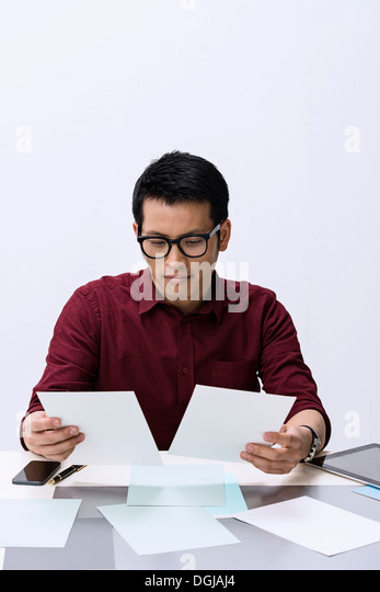 Young male designer looking at color samples - Stock Image
