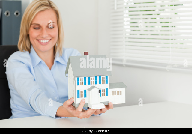 Smiling woman showing model house - Stock Image