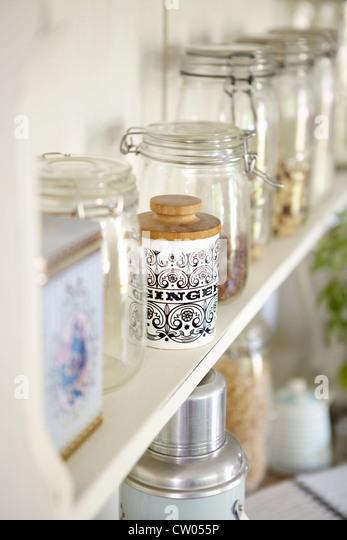 Jars of dried foods on shelf - Stock Image