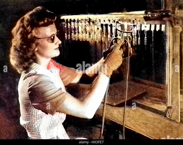 A female worker wearing dark glasses tests vacuum tubes for Bell Systems, 1922. Note: Image has been digitally colorized - Stock Image