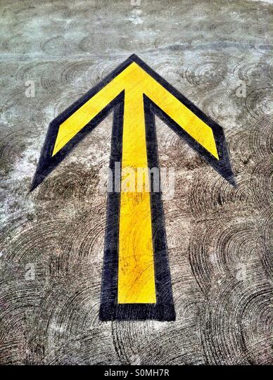 Yellow directional arrow on pavement in parking structure - Stock-Bilder