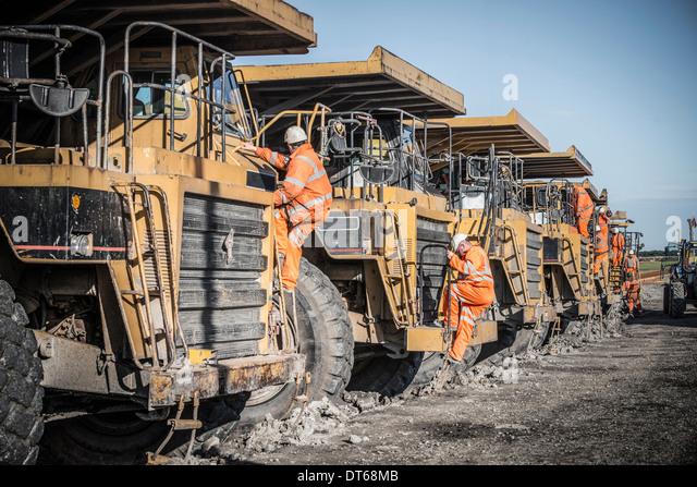 Dumper truck drivers climb down for break at surface coal mine - Stock Image