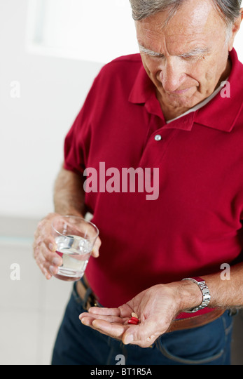 senior man taking medicine - Stock Image