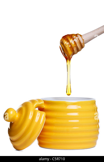 Photo of a yellow beehive shaped honey pot with dripping dipper held above, isolated on a white background. - Stock Image