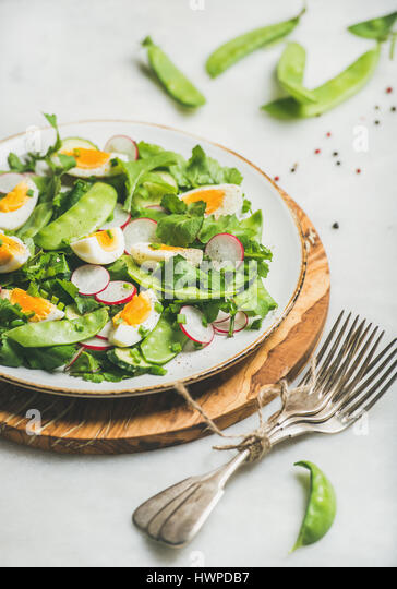 Spring salad with radish, boiled egg, arugula, green pea, mint - Stock Image